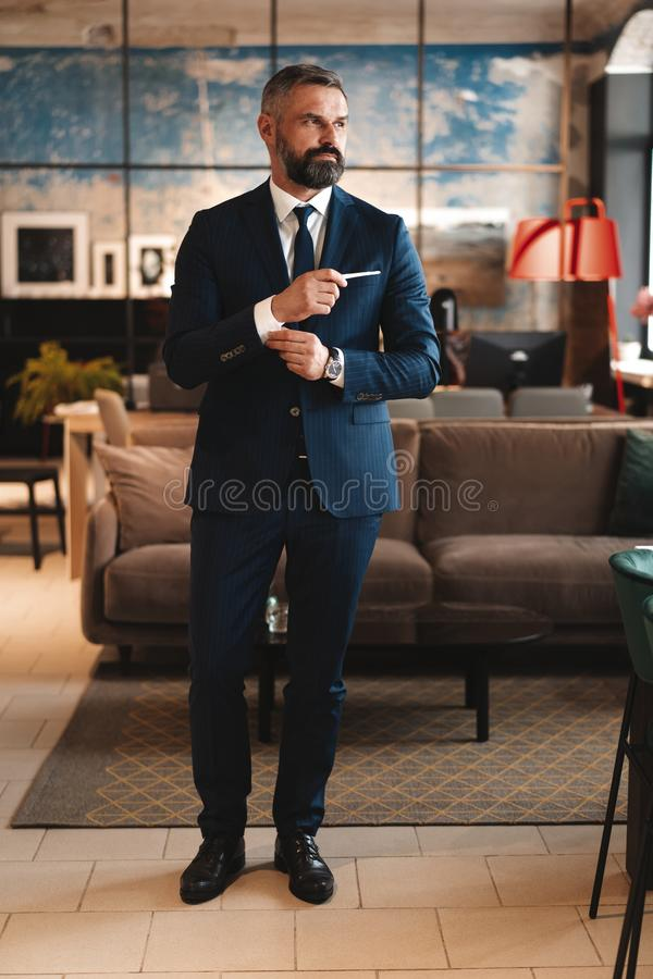 Stylish bearded man in a suit standing in modern office royalty free stock images