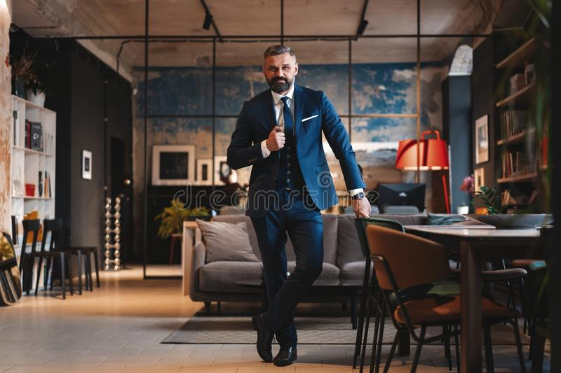 Stylish bearded man in a suit standing in modern office. Success concept. Stylish bearded man in a suit standing in modern office stock image