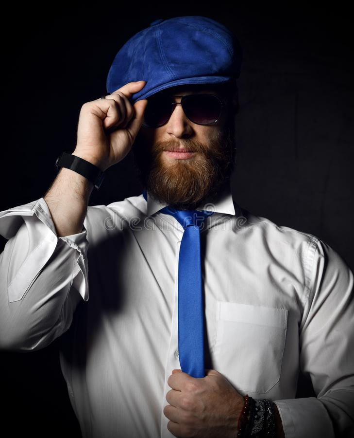 Bearded gentleman in white shirt and sunglesses holds his blue cap hat and tie greeting stock image