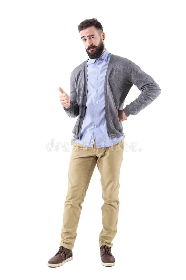 Stylish bearded smart casual guy wearing cardigan showing thumb up gesture and look at camera. Full body length portrait isolated on white background stock photo