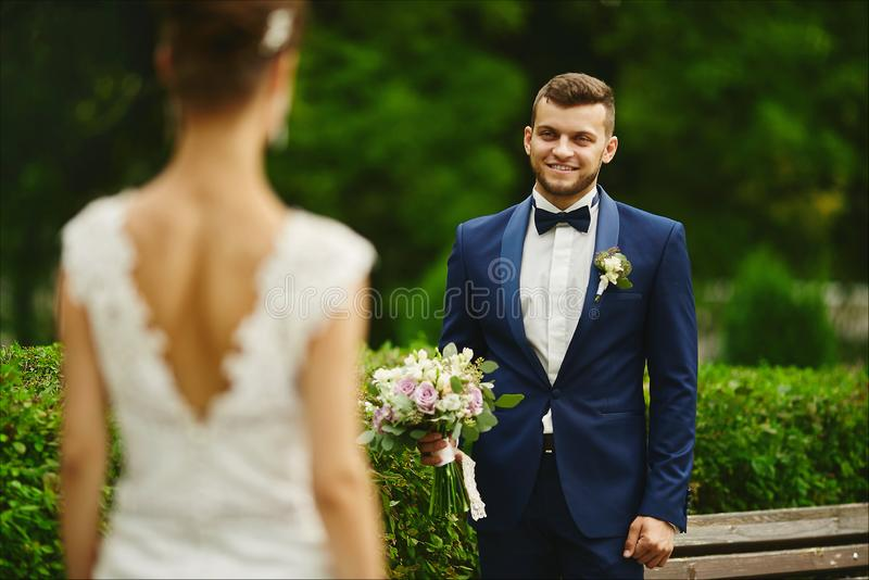 Stylish and bearded young brutal man in a smart suit holding the bouquet and looking on his sexy and beautiful model royalty free stock photography