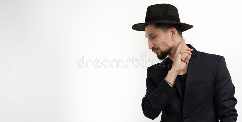 Stylish bearded young man in black trendy suit and hat holding hand near face, looking down left isolated over white stock images
