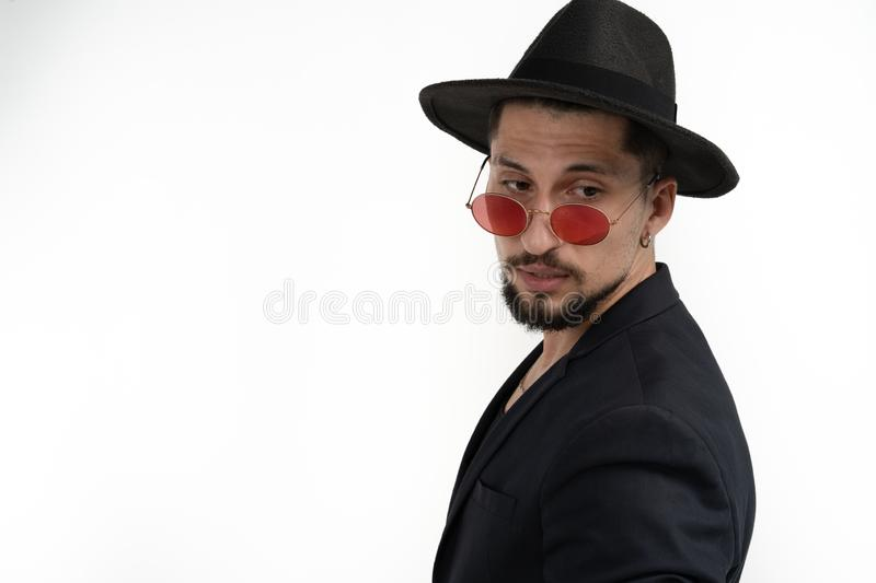 Stylish bearded young man in black trendy suit and hat in red sunglasses, looking down right isolated over white royalty free stock images