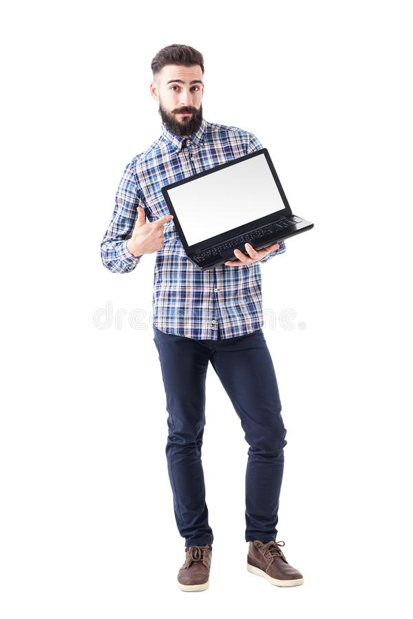 Stylish bearded young man pointing finger on blank laptop screen looking at camera stock photo