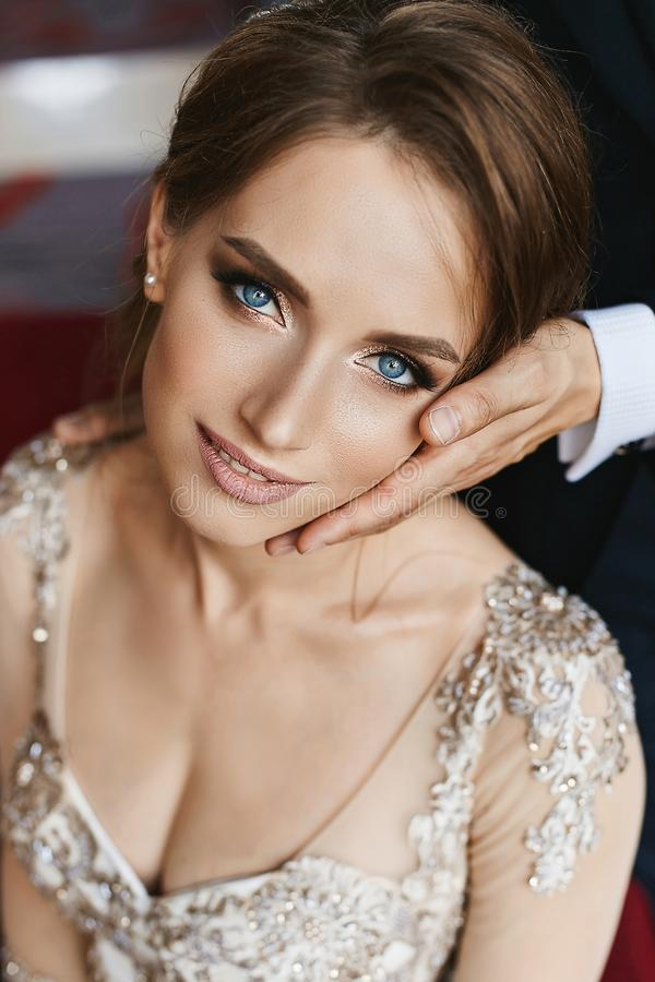 Stylish and beautiful brown-haired model girl with wedding hairstyle and bright makeup in stylish lace dress lean on stock photography