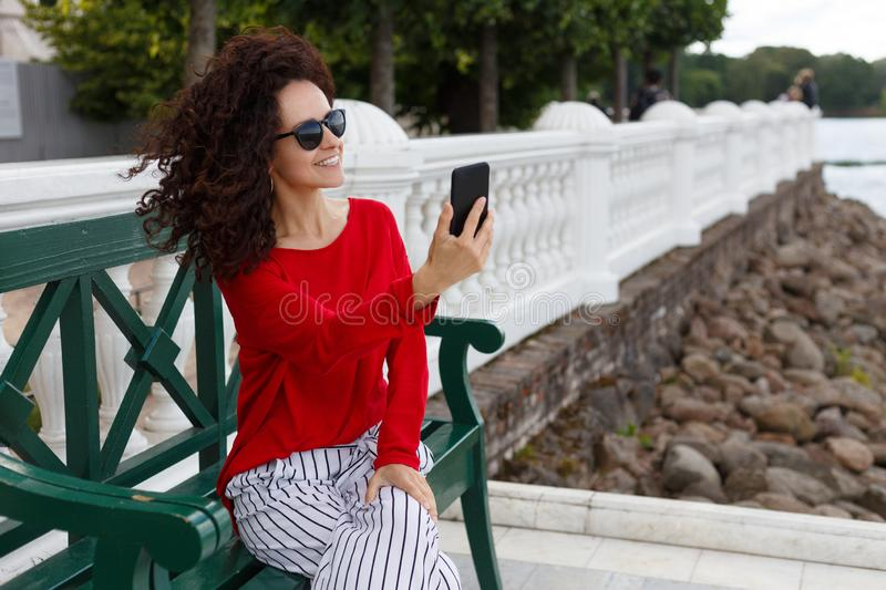 Young beautiful curly woman in sunglasses, doing selfie on a smartphone at the park. Background in summer port. royalty free stock photography