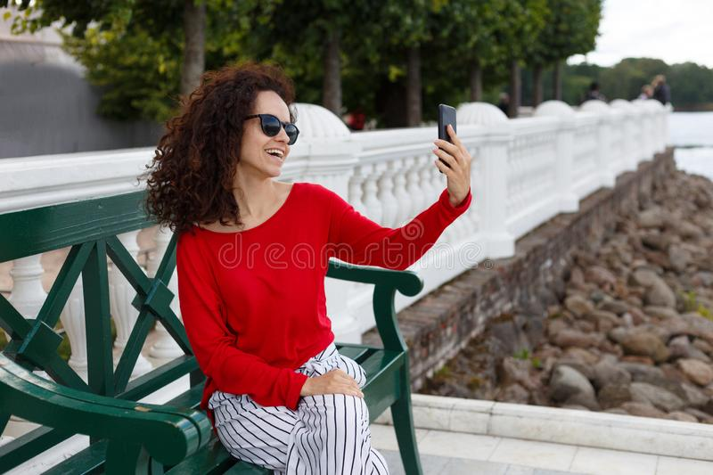 Stylish beautiful curly woman in sunglasses doing selfie on a smartphone, seated on a green bench in the park. royalty free stock photos