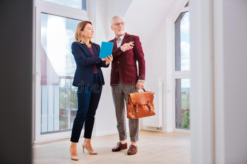 Stylish beautiful estate agent wearing blue costume talking to her client stock image