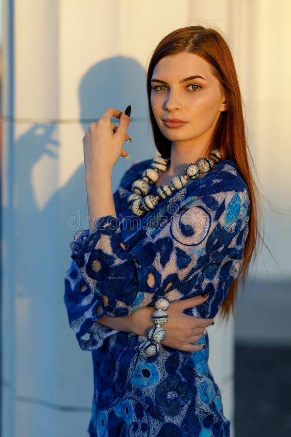 Stylish beautiful girl in designer clothes. Model poses in a tunic. Painting is based on Russian porcelain painting - Gzhel, close-up royalty free stock photography