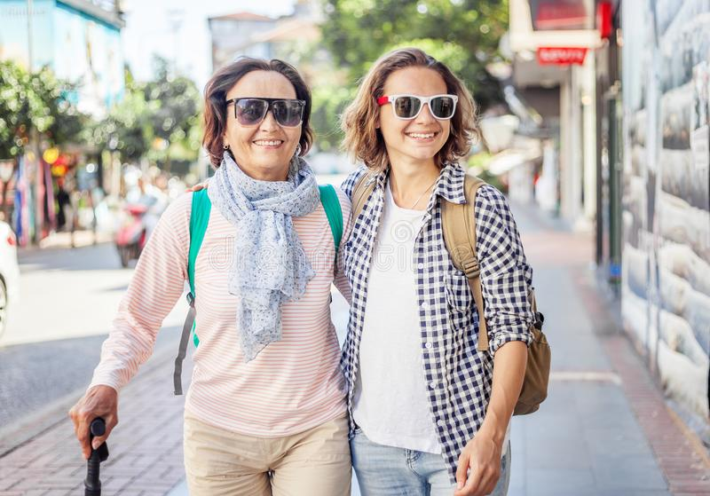 Stylish and beautiful mature mother and adult daughter are walking along the street. Family, travel, shopping, joy, communication stock photos
