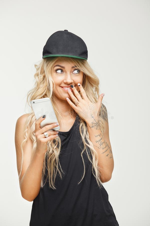 Stylish and beautiful woman with long blond hair holds phone in hands, puts palm to mouth, demonstrating surprise over. White isolated. Funny female emotion stock image