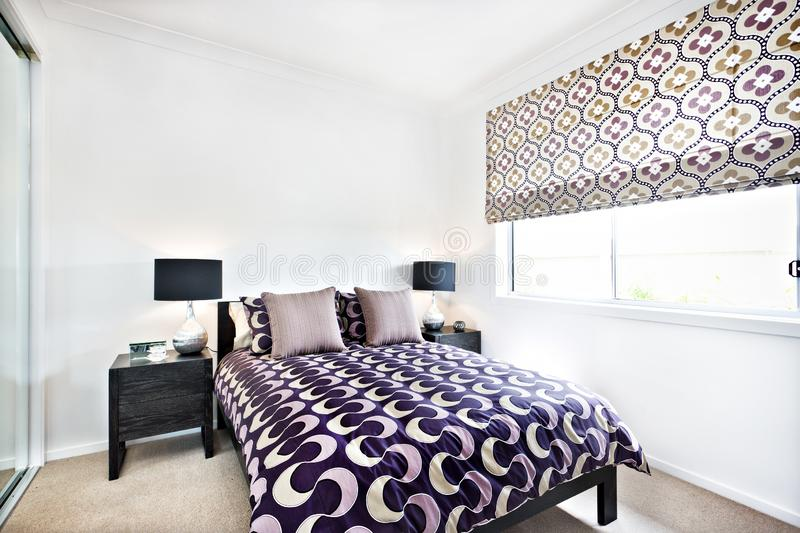 Stylish bedroom with abstract designs and sunlight through the window royalty free stock image