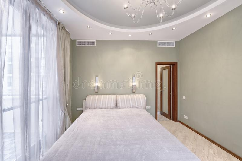 Modern interior of a bedroom in the new house. Stylish bedroom interior with double bed royalty free stock images