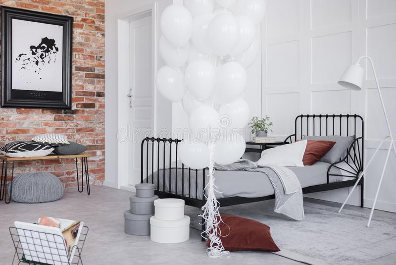 Bedroom interior with grey bedding, bunch of white balloons and black frame on the brick wall, real photo stock image