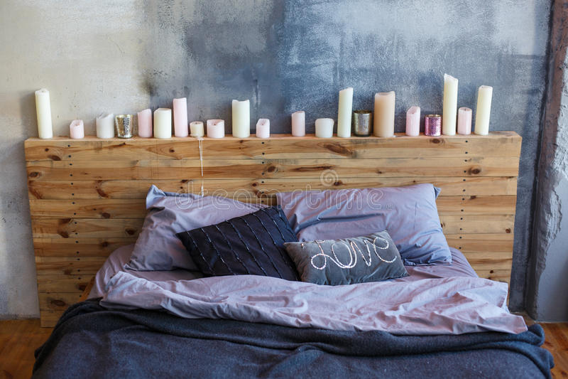 Stylish bedroom in loft style with grey colors and many candles. stock photography