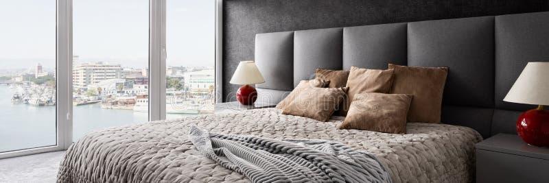 Stylish bedroom with window wall royalty free stock image