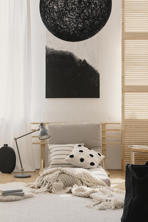 Stylish black chandelier and black and white abstract painting in japanese inspired beige bedroom royalty free stock image