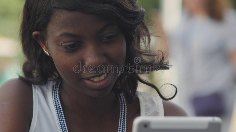Stylish black female woman working with modern tablet outdoor in summer city stock images