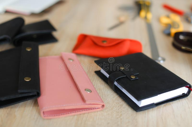 Stylish black and pink handmade leather wallets and notebook lying on table. stock photos