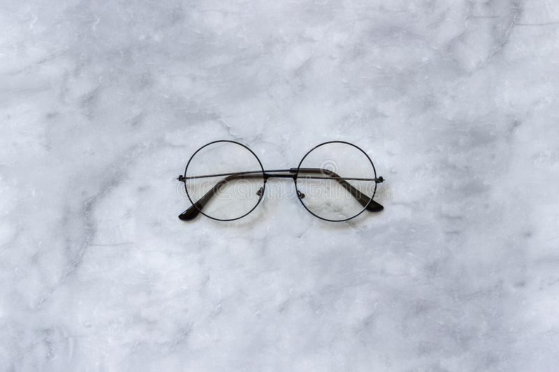 Stylish black round eyeglasses spectacles on marble background. Top view Copy space Minimal style stock images