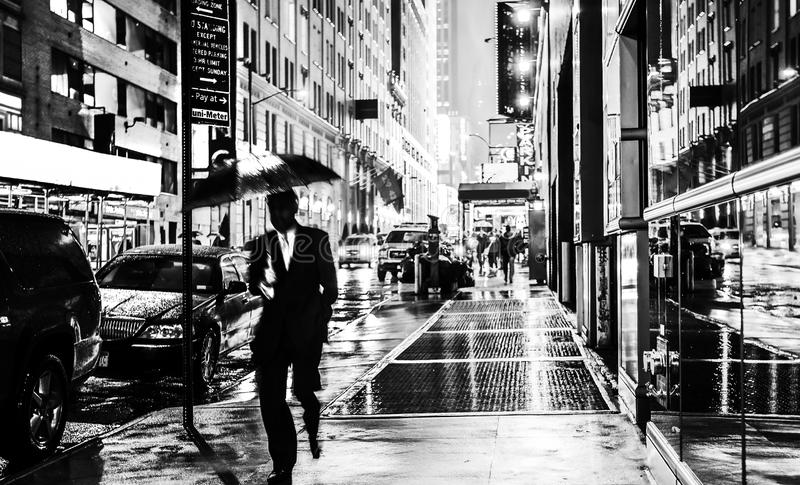 Stylish black and white wet New York NYC commuter with umbrella. Stylish black and white wet New York street photography image of a commuter with umbrella royalty free stock photography