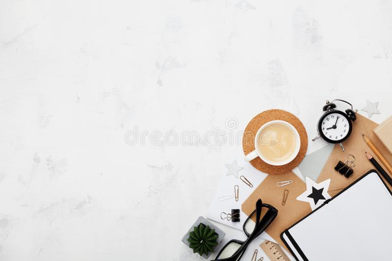 Stylish blogger working desk with coffee, office supply, alarm clock and clean notebook on white table top view. Flat lay. Copy space for text