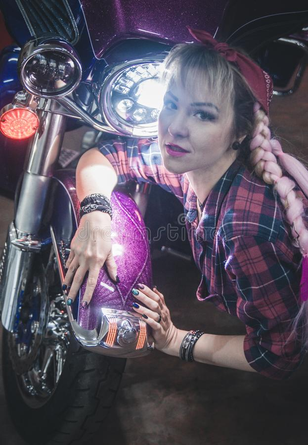 Stylish blond woman posing with motorcycle. Stylish woman posing on motorcycle stock photography