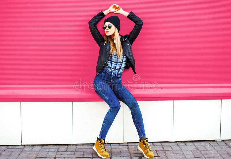 Stylish blonde girl model in full-length posing wearing rock black style jacket, hat on city street over colorful pink wall. Background royalty free stock photo