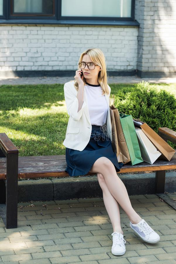 stylish blonde girl with shopping bags sitting on bench and talking stock images