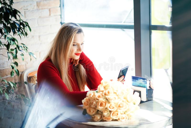 Stylish blonde woman with roses and red lipstick in restaurant plays with mobile phone in sunny day stock photo