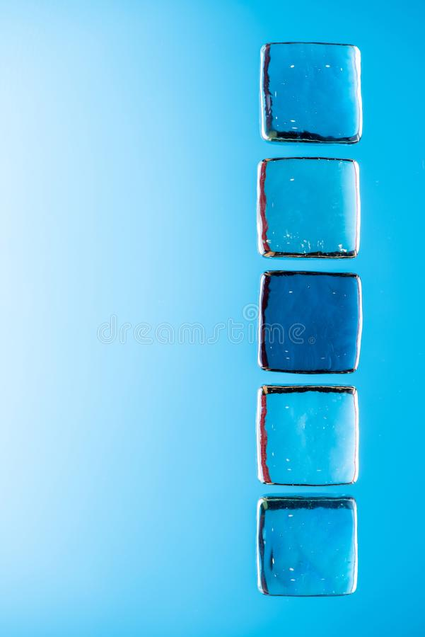 Stylish blue background with transparent ice-like cubes for drinks. Flat lay macro photo royalty free stock photos