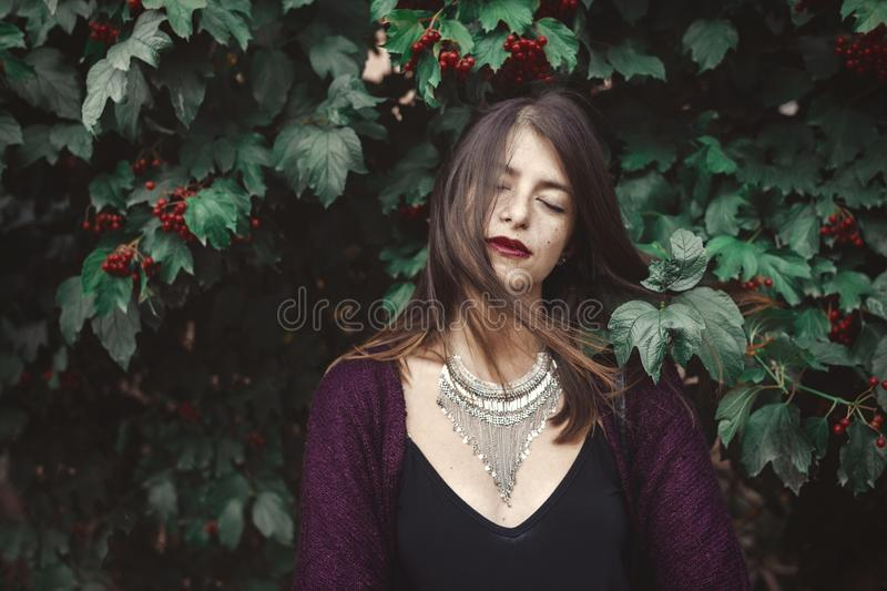 Stylish bohemian girl with modern jewelry posing under green branches of guelder rose in street. Hipster girl calm portrait among stock photos