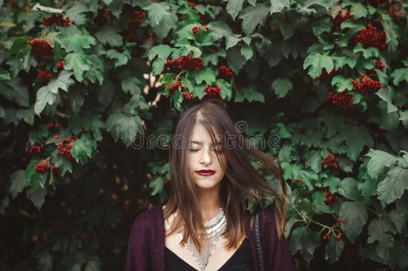 Stylish bohemian girl with modern jewelry posing under green branches of guelder rose in street. Hipster girl calm portrait among stock photo