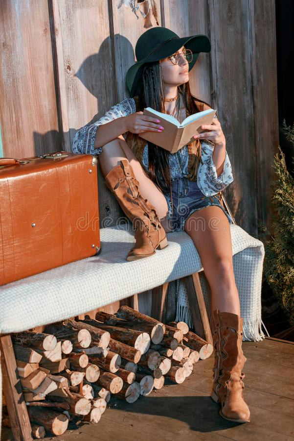 Stylish bohemian girl reading a book sitting on a bench in a. Wooden house royalty free stock photo