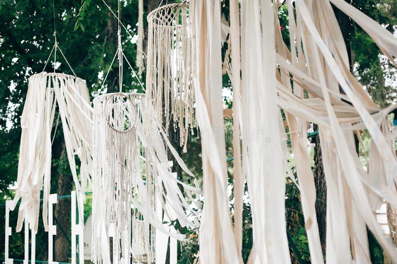Stylish boho decor on trees. Modern bohemian decoration of white macrame and ribbons, hanging on branches in summer park. Wedding royalty free stock photos