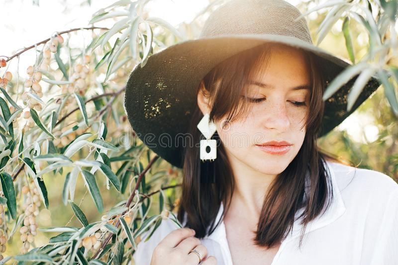 Stylish boho girl in hat and with modern earrings posing among green olive branches in soft evening light. Young fashionable woman stock image