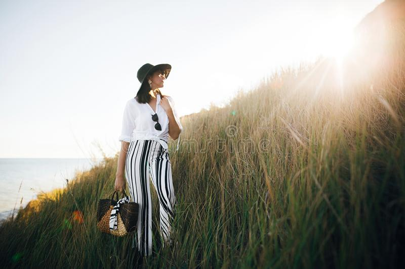 Stylish boho girl in hat posing among grass in sunny evening light at sandy cliff near sea. Happy young fashionable woman relaxing. On tropical island beach stock images