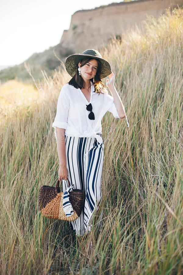 Stylish boho girl in hat posing among grass in sunny evening light at sandy cliff near sea. Happy young fashionable woman relaxing. On tropical island beach royalty free stock images