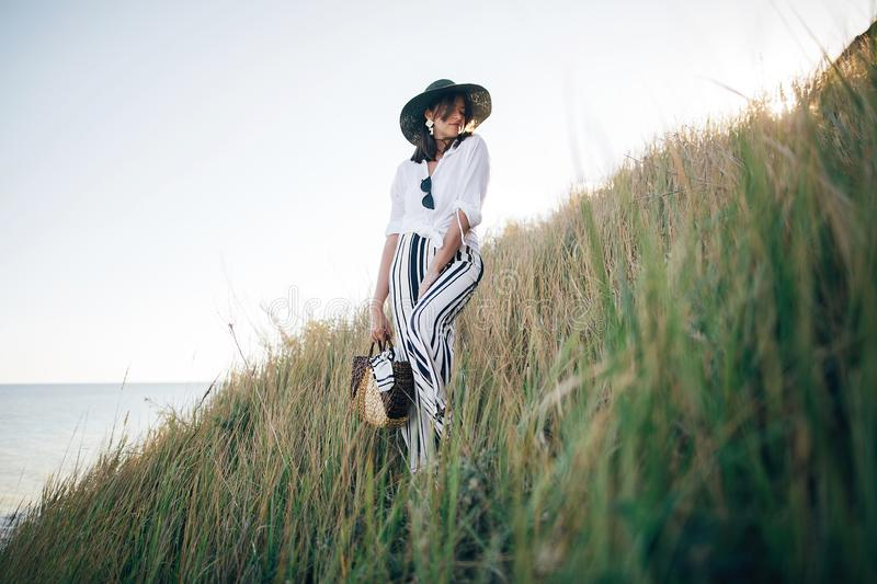 Stylish boho girl in hat posing among grass in sunny evening light at sandy cliff near sea. Happy young fashionable woman relaxing. On tropical island beach royalty free stock photo