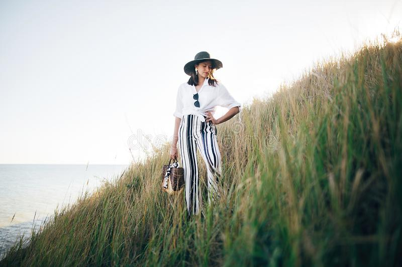 Stylish boho girl in hat posing among grass in sunny evening light at sandy cliff near sea. Happy young fashionable woman relaxing. On tropical island beach royalty free stock photos