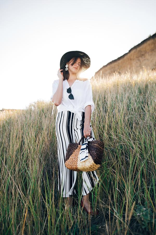 Stylish boho girl in hat posing among grass in sunny evening light at sandy cliff near sea. Happy young fashionable woman relaxing. On tropical island beach royalty free stock photography