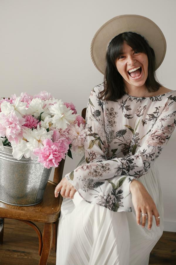 Stylish boho girl in hat sitting and laughing at metal bucket with peonies on rustic wooden chair. Beautiful hipster woman posing stock photo