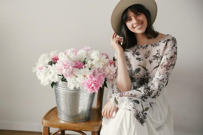 Stylish boho girl in hat sitting at metal bucket with peonies on rustic wooden chair.Beautiful hipster woman smiling at big royalty free stock photography