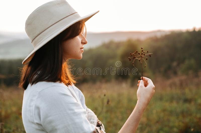 Stylish boho girl holding dried herb in sunny light at atmospheric sunset in meadow. Calm hipster woman in poncho and hat enjoying. Traveling in evening stock photos