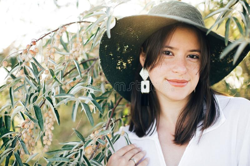 Stylish boho girl with modern earrings posing among green olive branches in soft evening light. Happy young fashionable woman stock photography