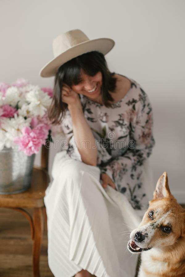 Stylish boho girl playing and smiling with cute golden dog at metal bucket with peonies on rustic wooden chair in home. Beautiful royalty free stock photos