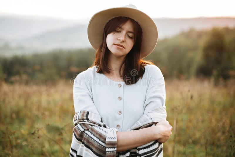 Stylish boho girl portrait in sunny light at atmospheric sunset in meadow. Calm hipster woman in poncho and hat enjoying traveling royalty free stock photography