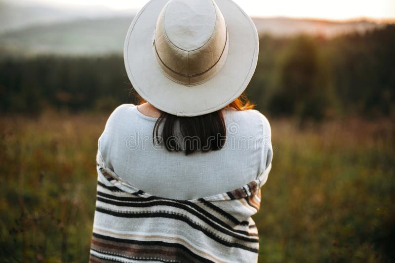 Stylish boho girl posing  in sunny light at atmospheric sunset in meadow. Happy hipster woman in poncho and hat enjoying traveling stock image