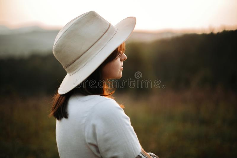 Stylish boho girl posing  in sunny light at atmospheric sunset in meadow. Happy hipster woman in poncho and hat enjoying traveling royalty free stock photos