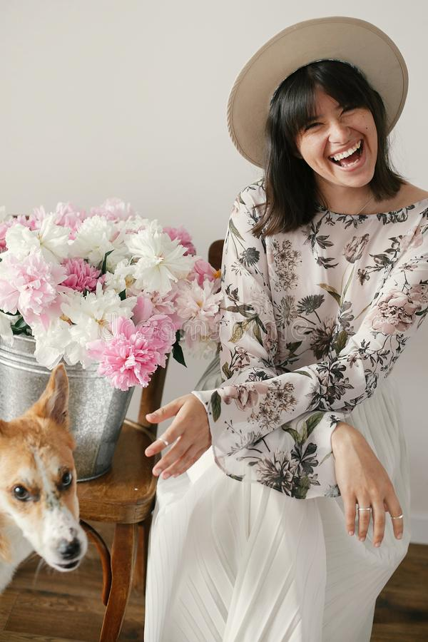 Stylish boho girl sitting at metal bucket with peonies on rustic wooden chair and playing with cute golden dog.Beautiful hipster stock image